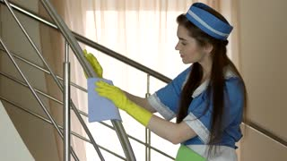 Housemaid with rag working. Girl in rubber gloves.