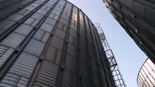 Huge metal buildings, up view. High metal grain storage facility. Look at the sky.