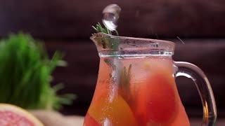 Ice falls into a grapefruit lemonade.