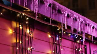 Icicles on the roof of the house. Christmas holidays. Warm winter. Melting icicles. Spring came.