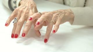 Imitation of the piano play with female hands. Old woman manicured hands in beauty salon imitating play on musical instrument, knocking with fingers on table.