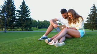 In love couple relaxing in the park. Guy and girl play games on the tablet. Communication on the Internet in the park. A date of lovers on the nature.