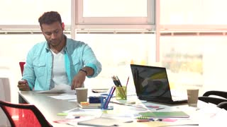 Indian designer working hard in office. Designer tired of work, huge bright windows background.