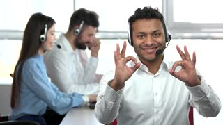Indian man in office showing OK gestures by two hands. Man pointing at his colleagues co-workers. Call center worker recommend his co-workers.