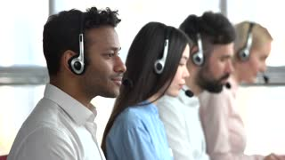Indian man turning head and smiling. Side view indian worker in tech support helping customer.