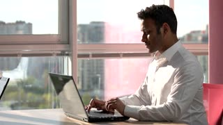Indian smiling programmer working on laptop. Concept of indian man typing on laptop in frame office with city view out of window.