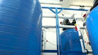 Industrial water filters. White pipes and red valves. Purification of water at plant. Newest equipment guarantees safety.