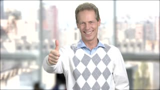 Intelligent man showing thumb up. Pleased mature man on window city background. Successful male entrepreneur.