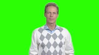 Intelligent smiling man on green screen. Happy mature man crossed arms standing on alpha channel background. Middle-aged cheerful man.