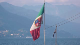 Italian flag on landscape background. Flag, water and mountains.