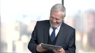 Joyful businessman playing on pc tablet. Happy cheerful senior man in formal wear using pc tablet on blurred background.