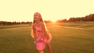 Joyful child playing with ball outdoors. Cute little girl throwing pink ball on green meadow background, slow motion. Kid having fun in countryside.