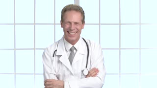 Joyful male doctor laughing and gesturing. Happy middle-aged doctor on window background. Human facial expressions.