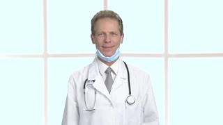 Joyful male doctor showing thumb up. Mature doctor in white coat gesturing thumb up while standing on window background. Operation was successfully completed.