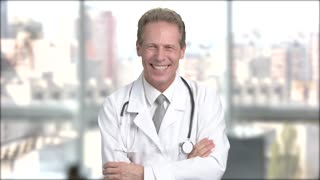 Joyful mature doctor on blurred background. Middle-aged doctor in white coat laughing on window city background.