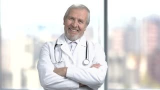 Joyful senior doctor with crossed arms. Cheerful elderly doctor folded arms on abstract blurred background. Happy medical specialist.