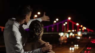 Just married look at the beautiful bridge. Romantic couple looking at the city in the evening lights. Old city in lights. Evening walk of loving couple.