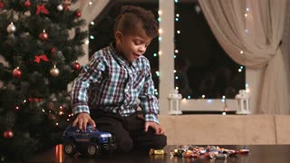 Kid near Christmas tree. Boy with candies. Joy of a child. Holiday presents and good mood.