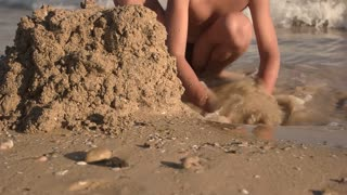 Kid on seashore, slow-mo. Boy is playing with sand.