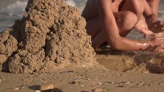 Kid on seashore, slow motion. Boy playing with wet sand.