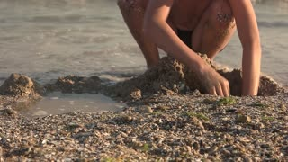 Kid on the shore, slow-mo. Boy digging pit in sand.