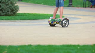 Kid riding on gyro scooter on cobbles road. Boy is driving through the park on a gyroboard.