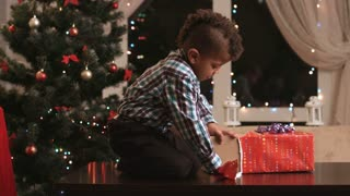 Kid unpacking gift on table. Toy and candies for present. Best presents for Christmas. Happy holidays guaranteed.