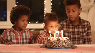 Kids blowing cake's candles out. Black boys blow candles out. No it's time to eat. Humble birthday party.
