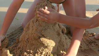 Kids building a sandcastle. Wet sand structure.
