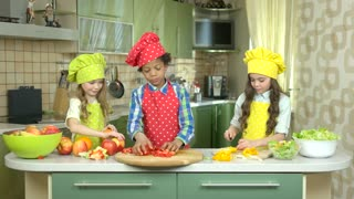 Kids cooking at kitchen table. Fruits and vegetables.