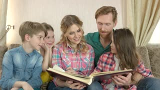 Kids kissing and hugging parents. Cheerful family with a book. The story of our happiness.