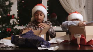 Kids open presents. Two boys near Christmas tree. Favorite holiday of children. Moments of joy.