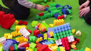 Kids playing constructor. Children playing with colorful plastic blocks. Kids building spaceship with lego bricks.