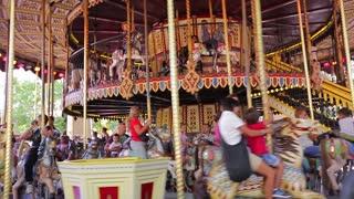 Kiev, Ukraine 21. 08. 2014. Retro carousel at an amusement park. People with kids fun ride on the carousel.