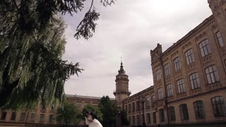 Kissing couple in park with old architecture.