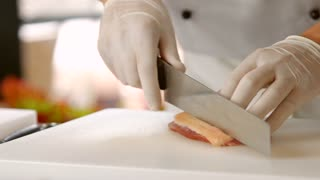 Knife making cuts on meat. Piece of meat with skin. Chef prepares duck breast. Ingredient for a poultry dish.