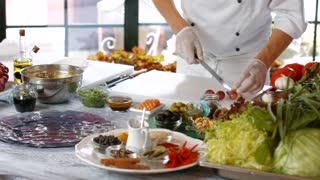 Knife quickly cuts grapes. Man cooks food at table. Skillful chef at work. Morning at bistro kitchen.
