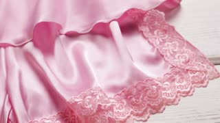 Lace ornament on pink silk. Cloth with ornament on display. Small lace inset on fabric. Suitable detail for thin material.