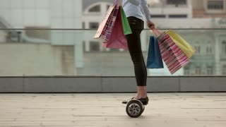 Lady holding shopping bags. Gyroscooter in slow motion.