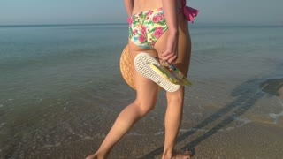 Lady in bikini walking, seashore. Young woman carrying beach hat.