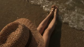 Lady in hat on seashore. Legs splashing water. Fun at the seaside.