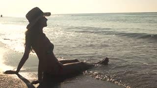 Lady sitting on seashore. Woman in bikini and hat. Beauty and infinity.