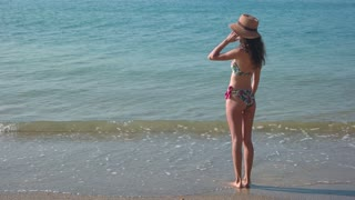 Lady standing on seashore. Slim woman in beach hat. Waiting for a miracle.