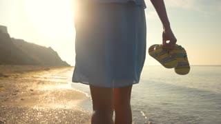 Lady walking on seashore. Woman is carrying flip flops.