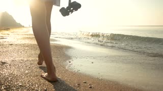 Lady with binoculars near sea. Barefoot woman in dress walking.