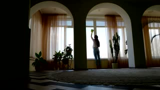 Lady with rag cleaning window. Busy woman indoors.