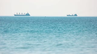 Large barges are floating on the sea. Transportation of ton of goods. Beautiful blue sea.