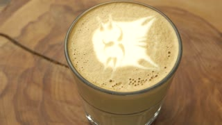 Latte glass with cat art. Coffee on wooden board spinning. Cute and tasty.