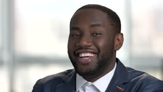 Laughing young black businessman. Close up face of happy charming afro american guy. Bright office, windows background.