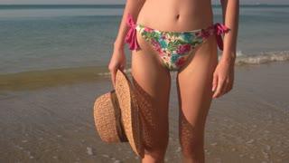 Legs in bikini dancing. Woman holding a beach hat.